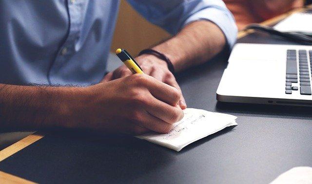 píšící muž za stolem