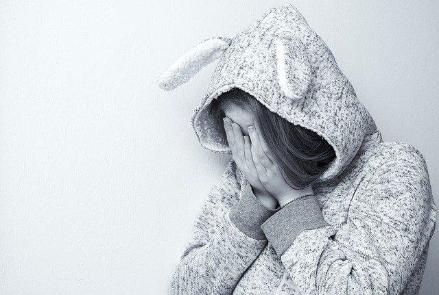 žena v kapuci která si zakrývá oči