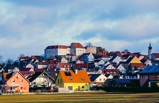 město, domy, modrá obloha, předtím kousek pole, v popředí žlutý dům s červenou střechou